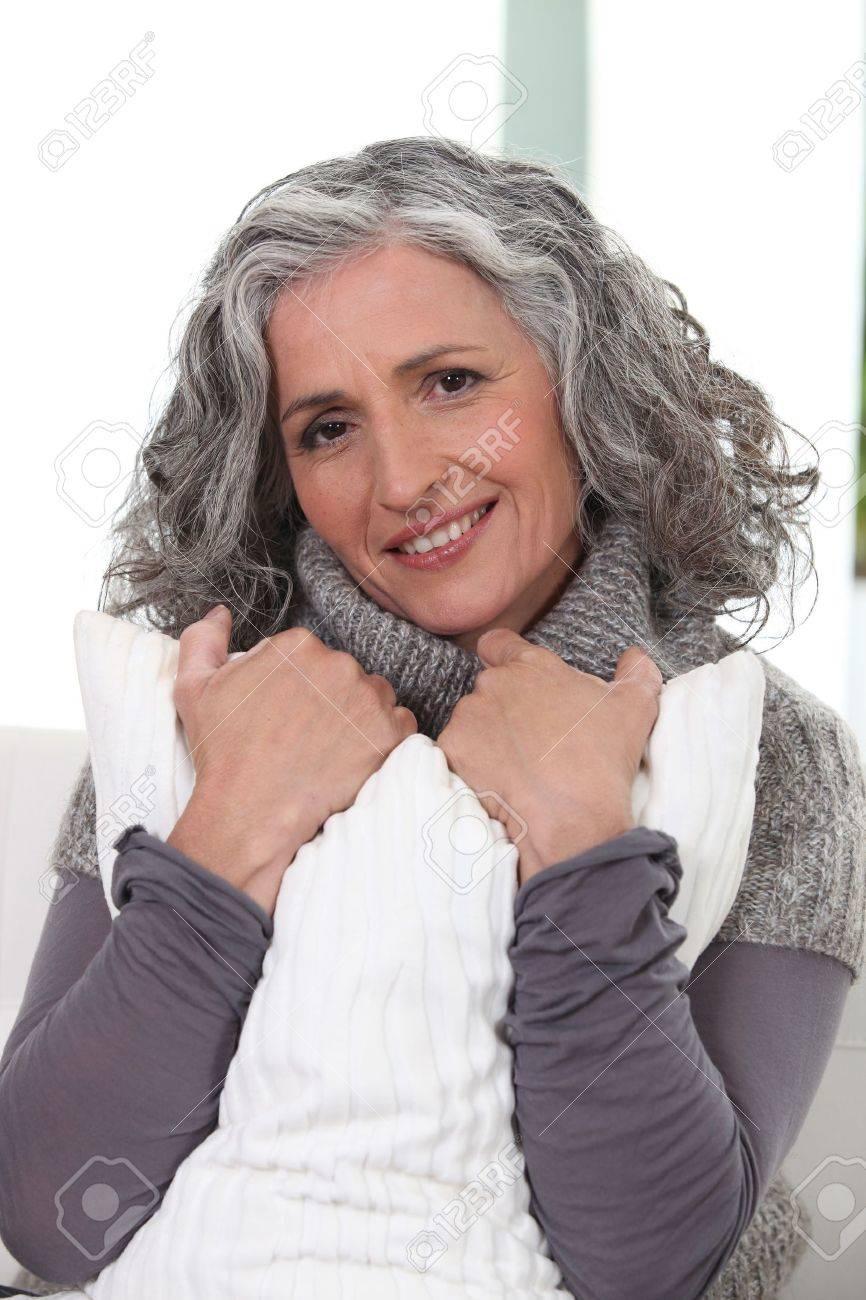 Stylish older woman holding a pillow Stock Photo - 14214014