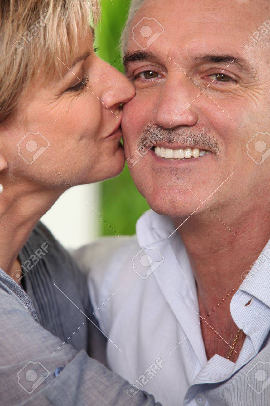 mature woman kissing a smiling man stock photo, picture and royalty