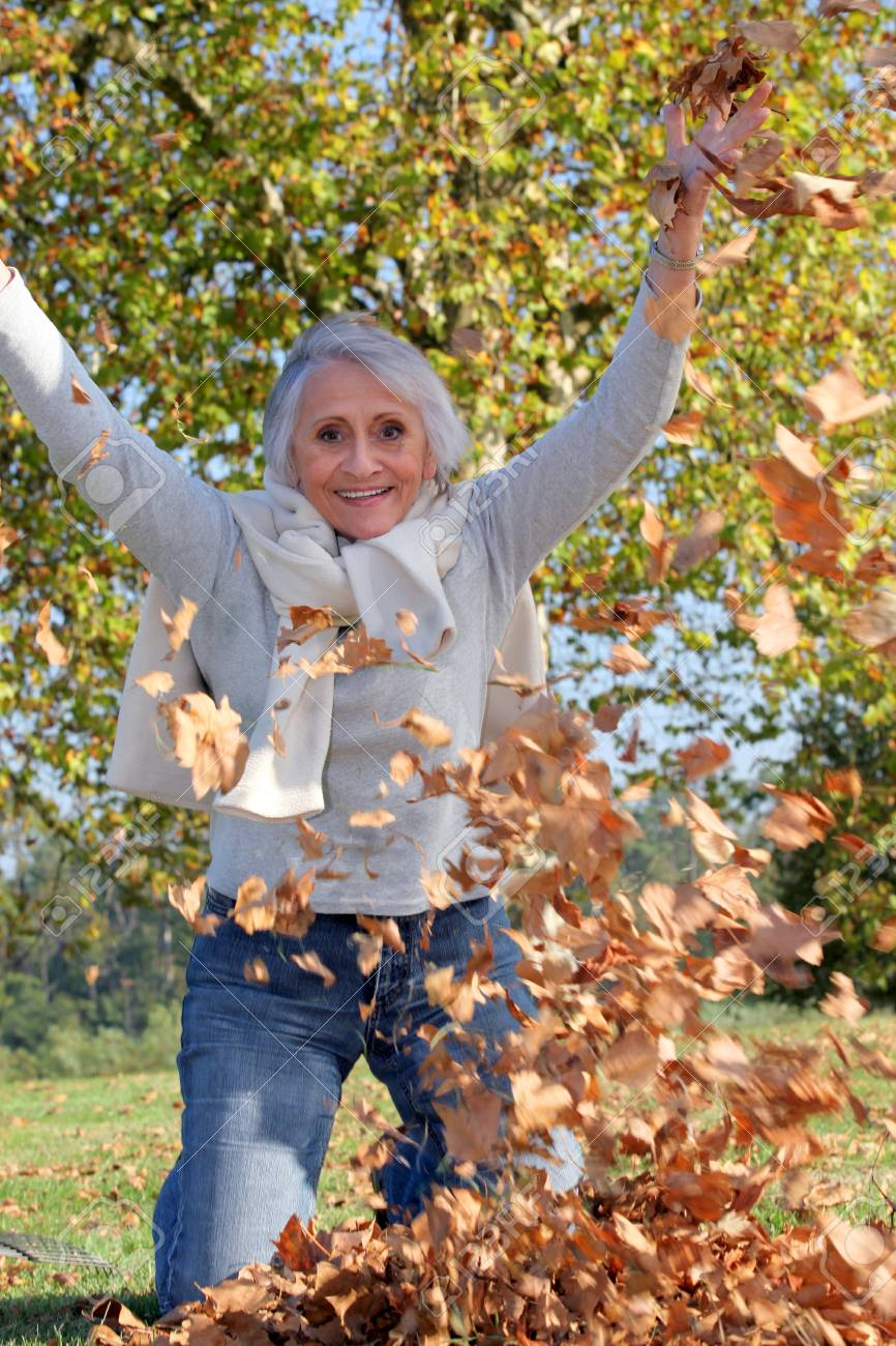 grandmother playing with a heap of dead leaves Stock Photo - 14203507
