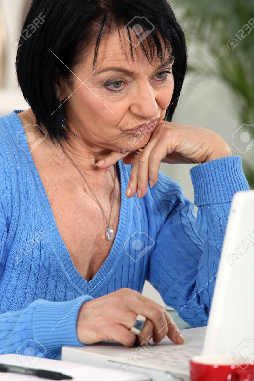Annoyed woman looking at her laptop Stock Photo - 14203463