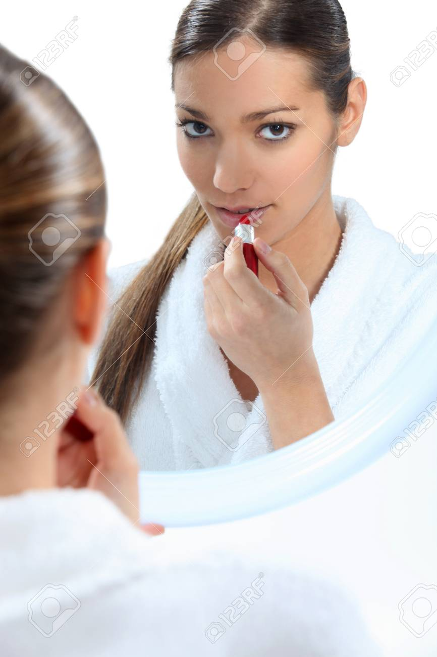 Young woman applying red lipstick Stock Photo - 15174959