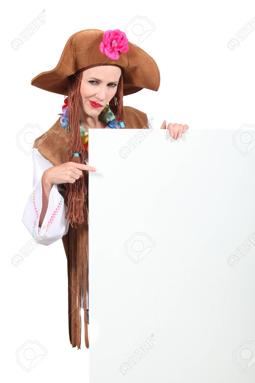 Woman in a seventies hippy costume pointing at a board left blank for your message Stock Photo - 15233271