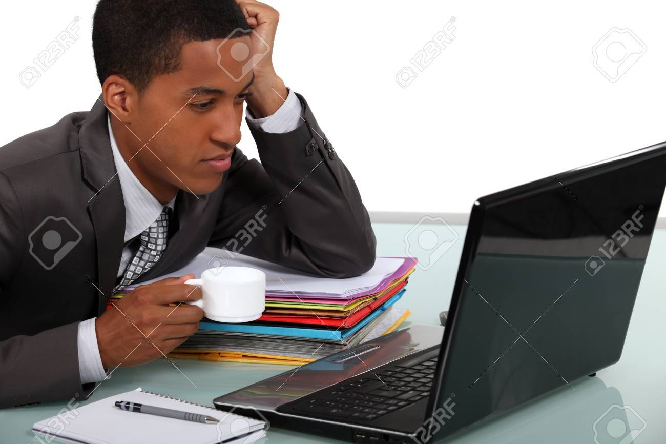 An African American businessman drinking a coffee while looking his laptop Stock Photo - 15391698