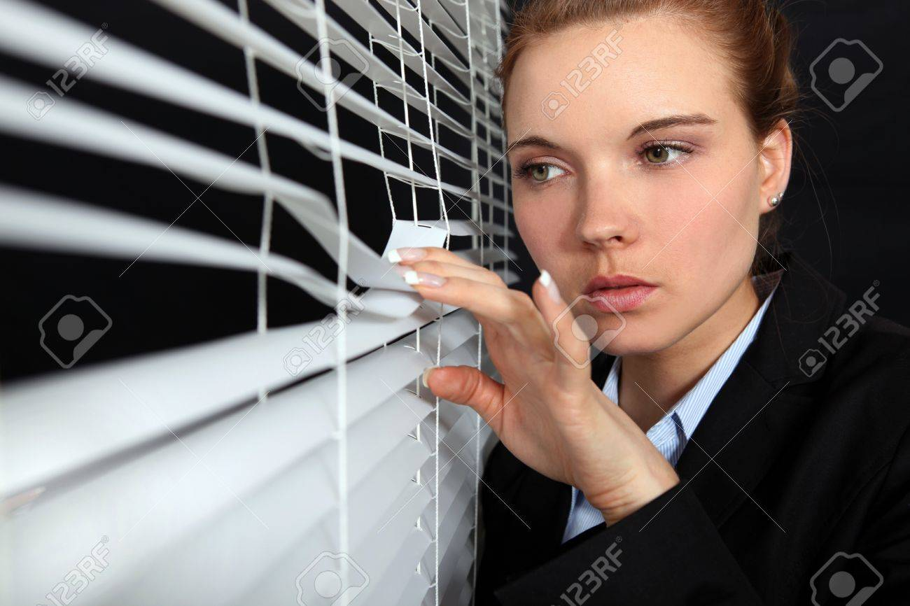 Woman looking through blinds Stock Photo - 15833033