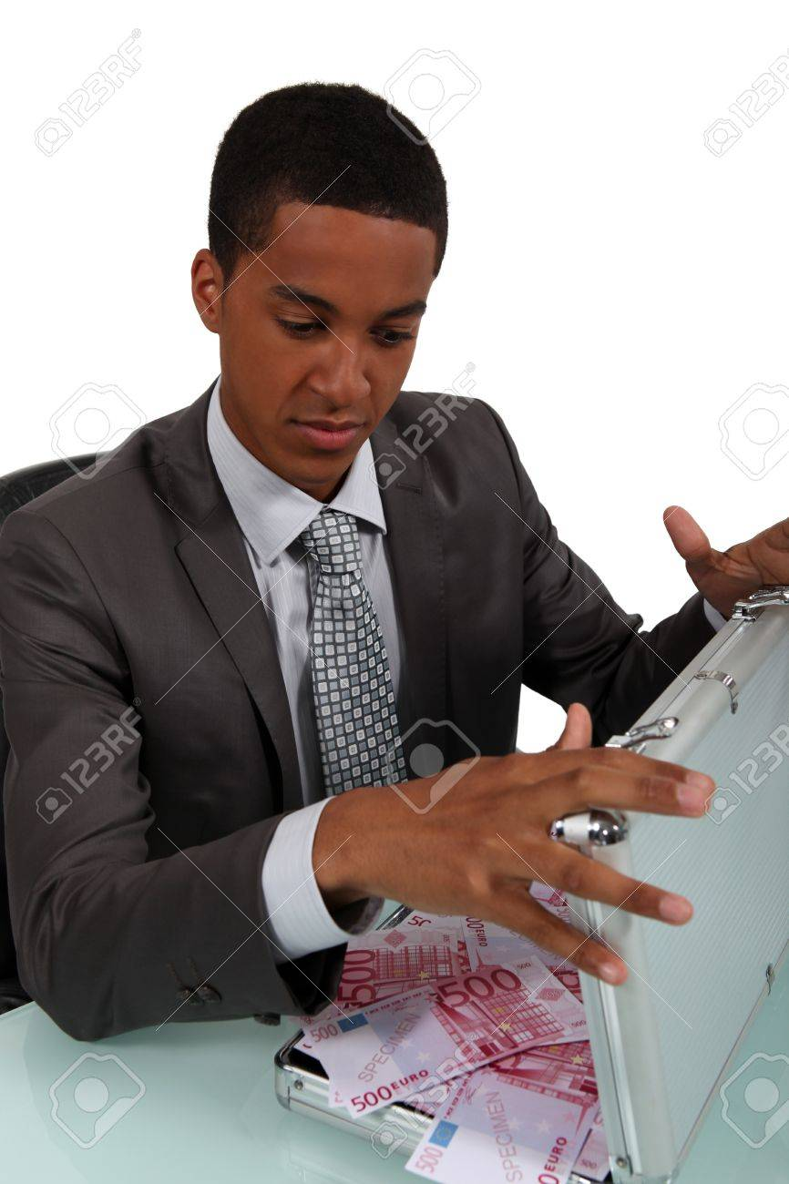 Businessman opening metal briefcase full of money Stock Photo - 15915933