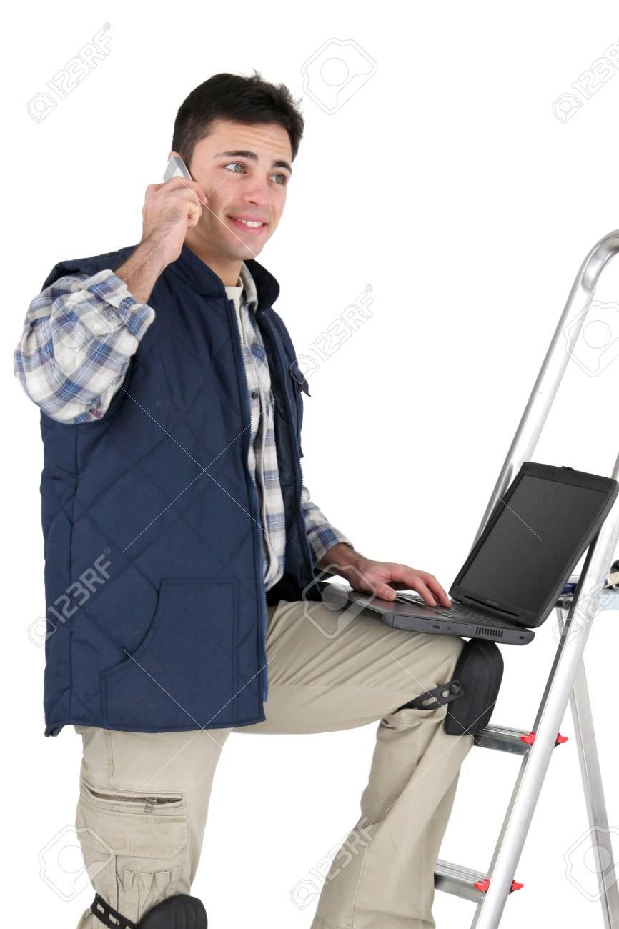 Decorator making telephone call whilst using laptop Stock Photo - 16552709