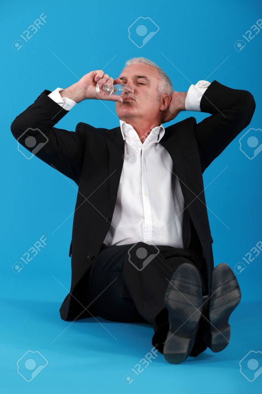Senior business sat on the floor with champagne flute Stock Photo - 16670074