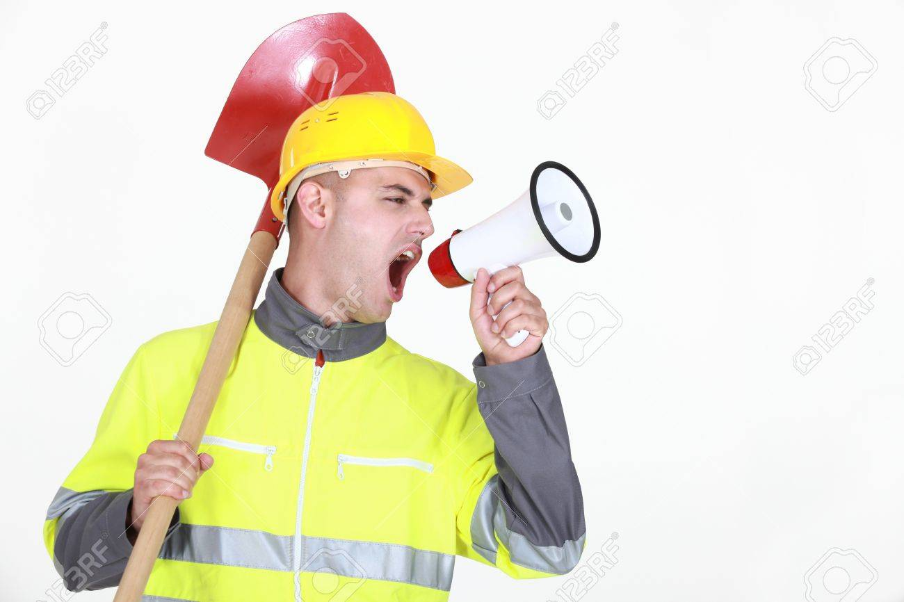Worker with a spade screaming into a bullhorn Stock Photo - 16731740