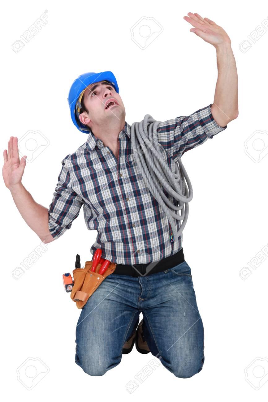 Kneeling laborer looking afraid Stock Photo - 16841933
