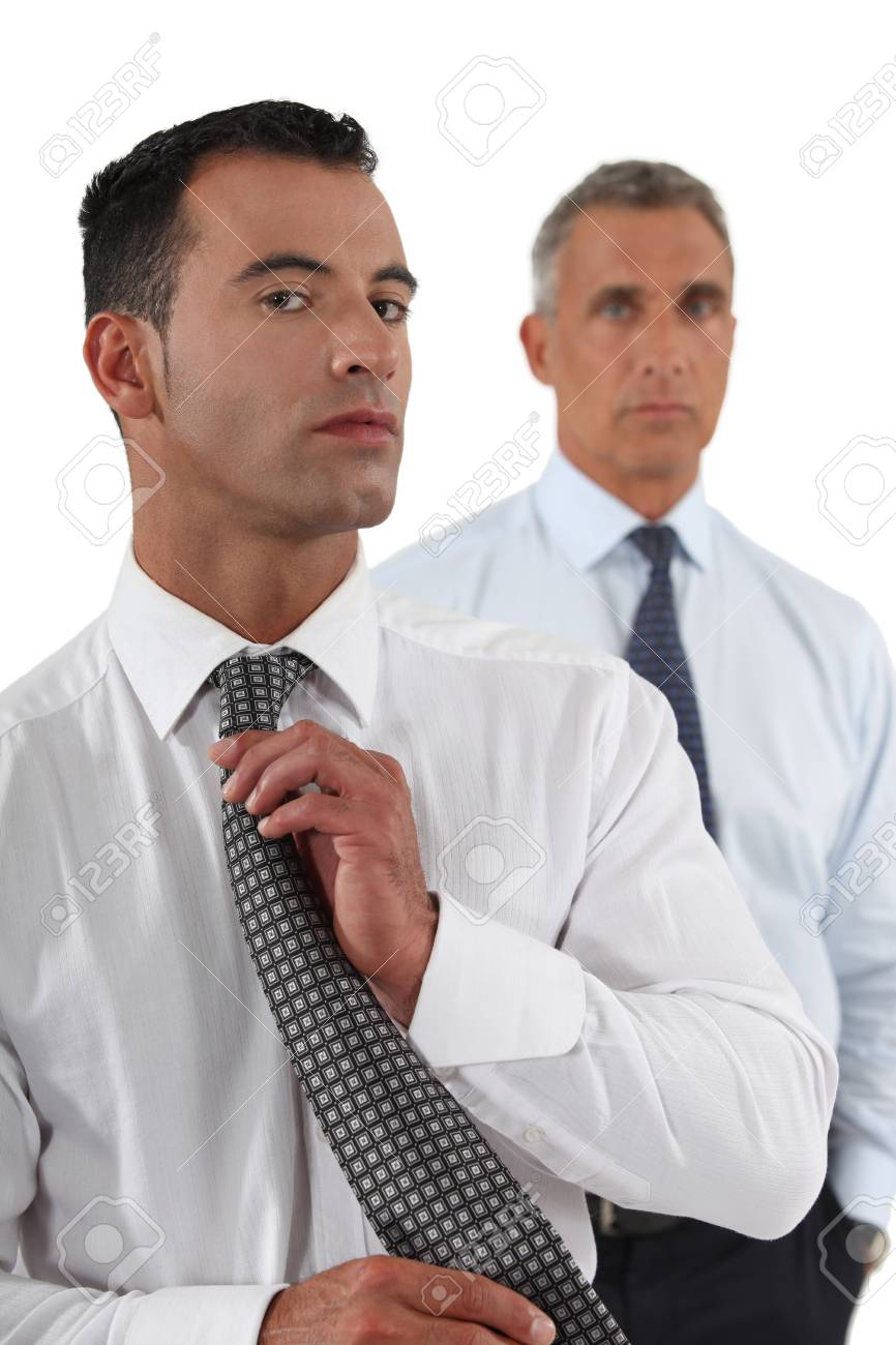 Businessman adjusting tie in front of colleague Stock Photo - 17220446