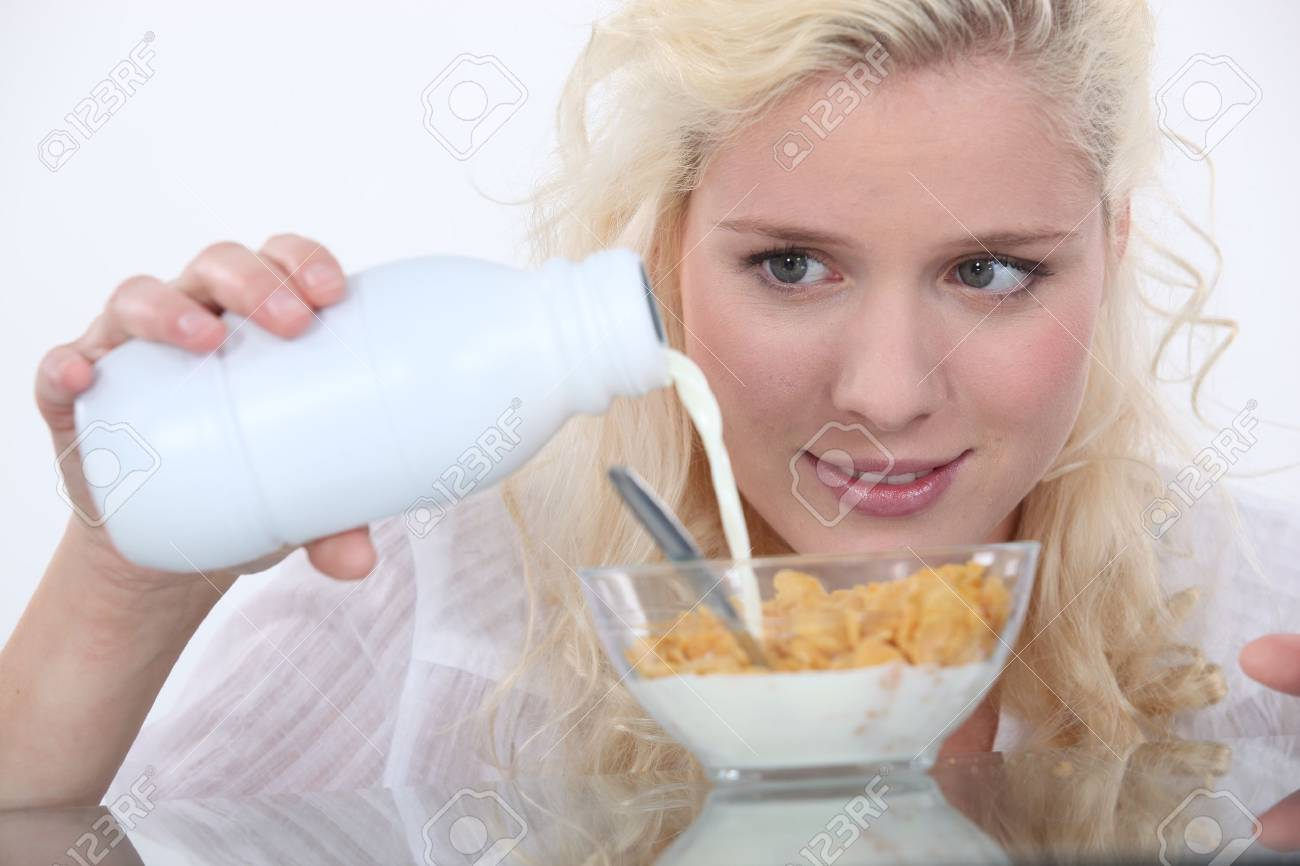Woman pouring milk into cereal bowl Stock Photo - 17480530