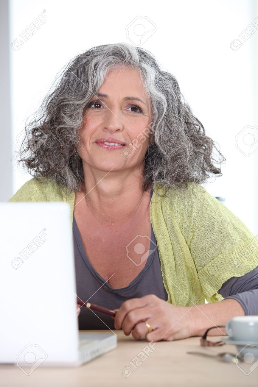Gray-haired woman in front of laptop computer Stock Photo - 17476219