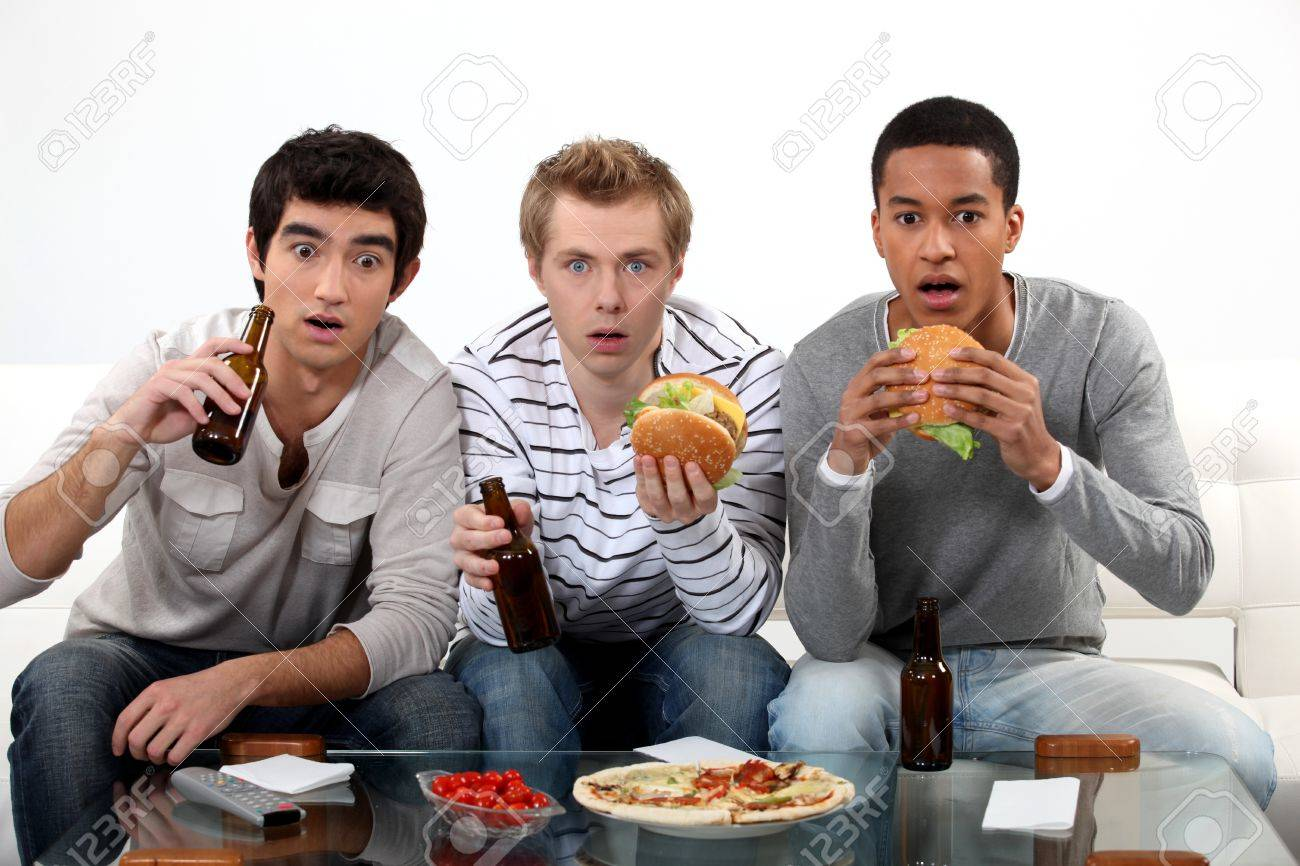 stunned men watching a horror film stock photo picture and stock photo stunned men watching a horror film