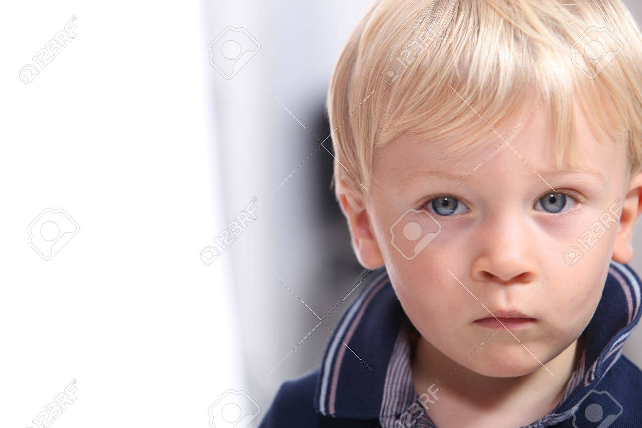 Landscape Portrait Of A Serious Little Boy With Blonde Hair And