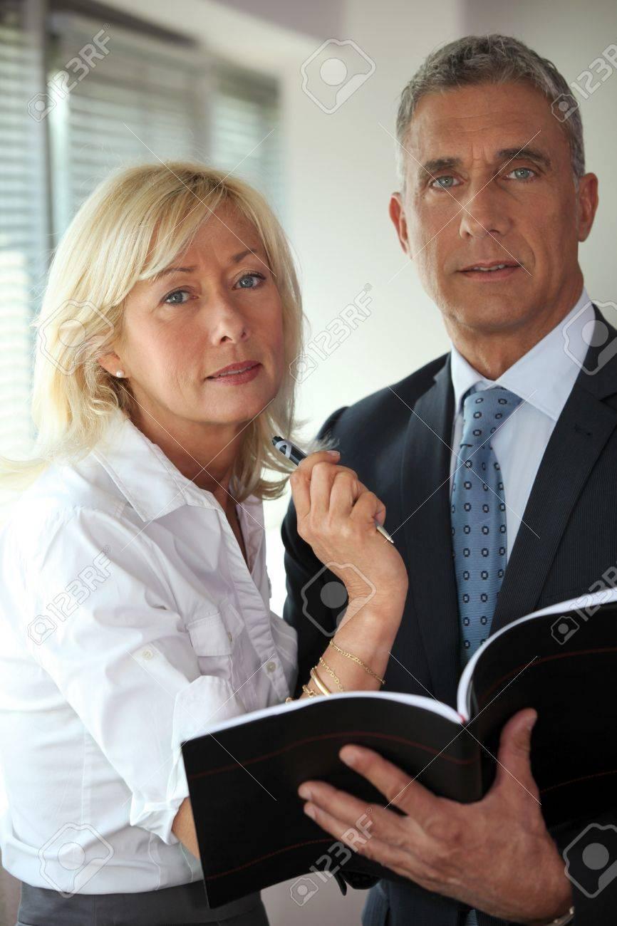 businessman and mature secretary consulting agenda stock photo