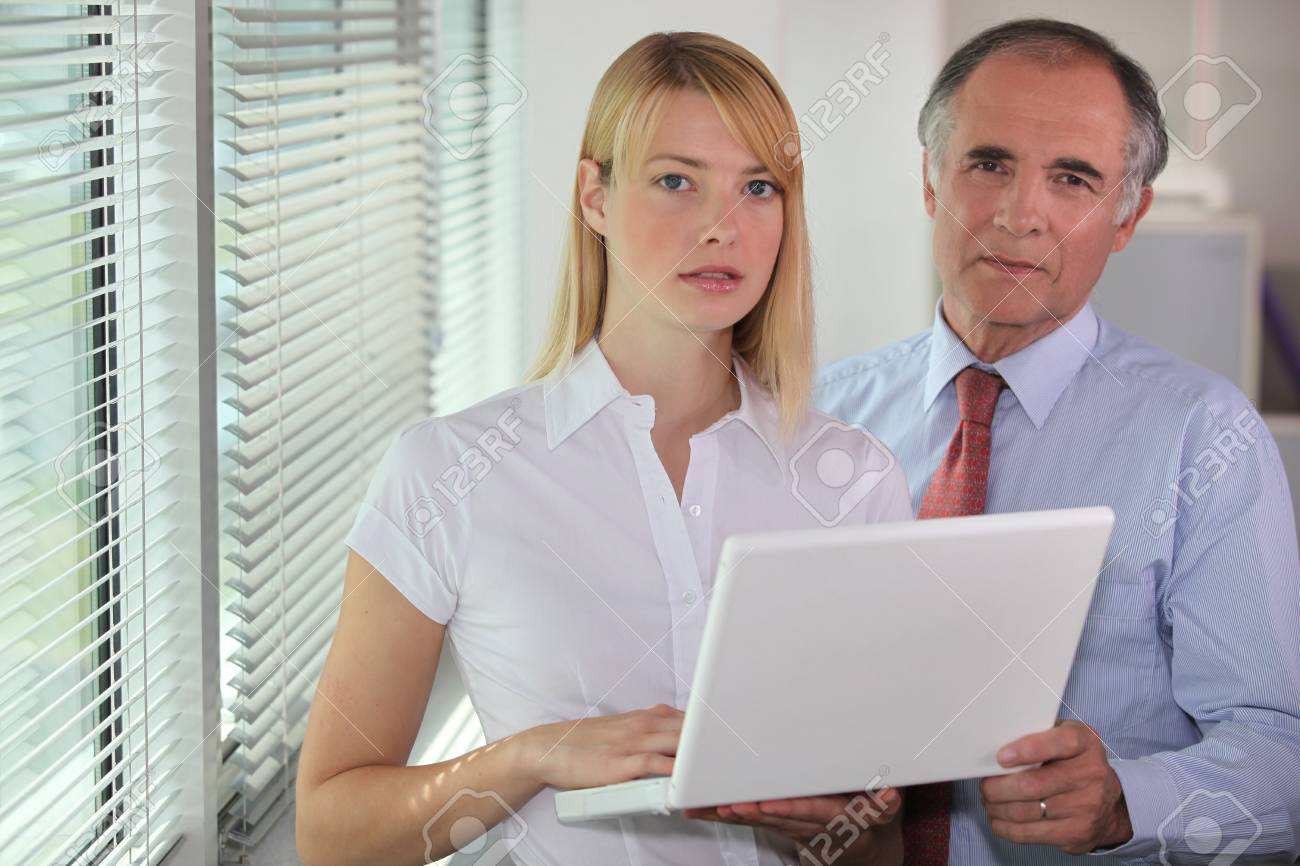 Businessman and his assistant looking at a laptop Stock Photo - 17977533