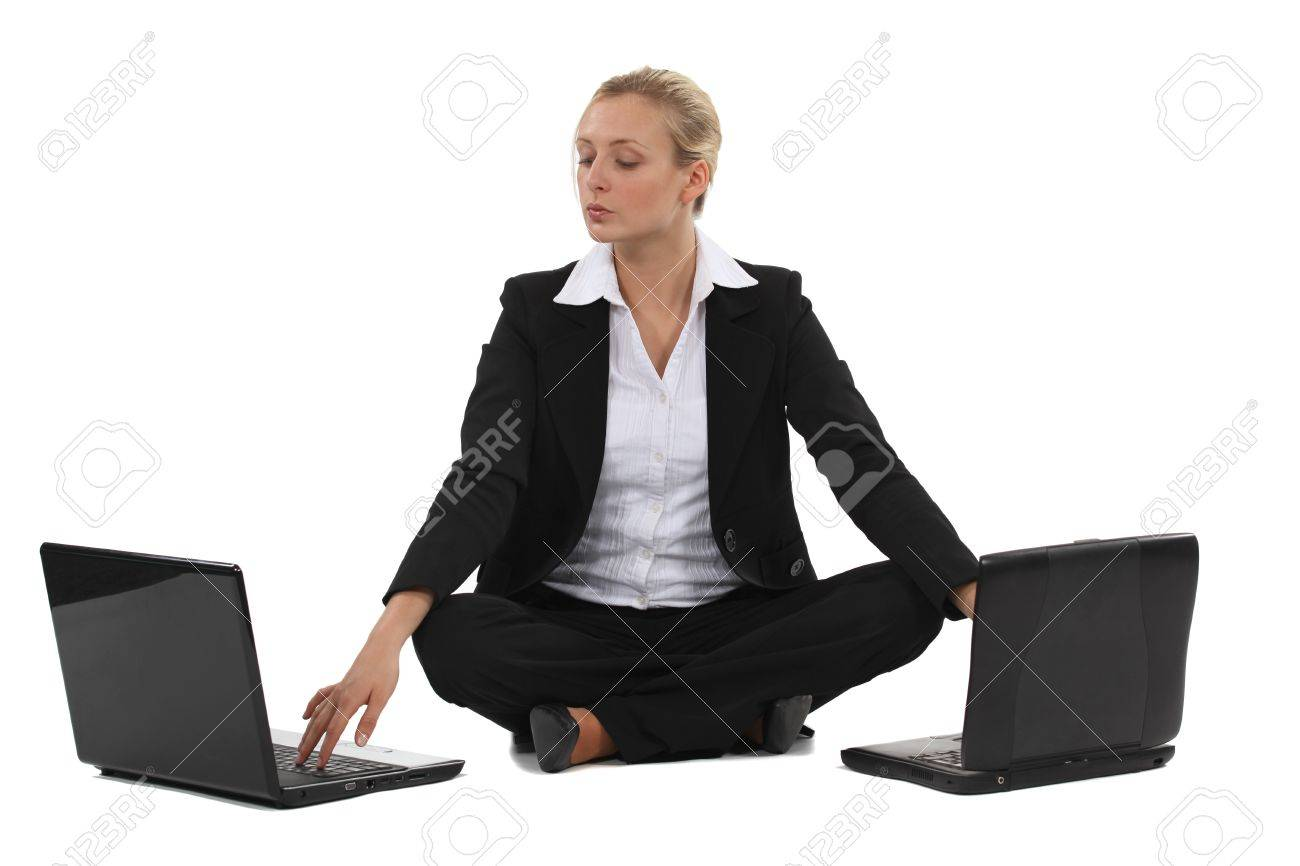 Blond businesswoman sat with two laptops Stock Photo - 18291899