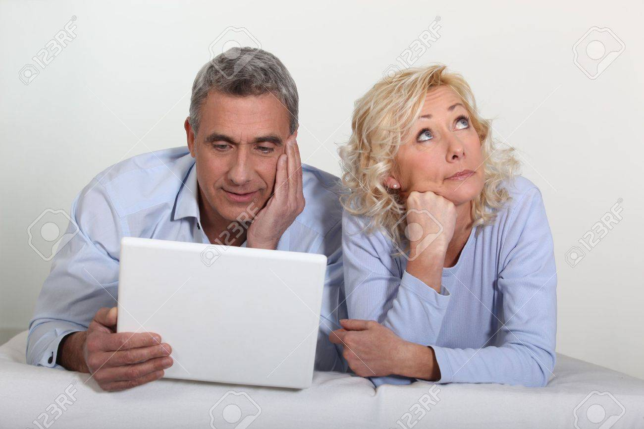 Middle aged couple with a laptop on their bed. Stock Photo - 18740893