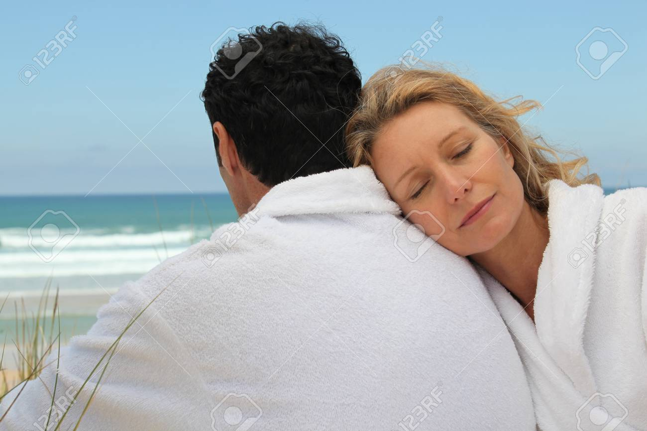Husband and wife on the beach in bath robes Stock Photo - 22255746