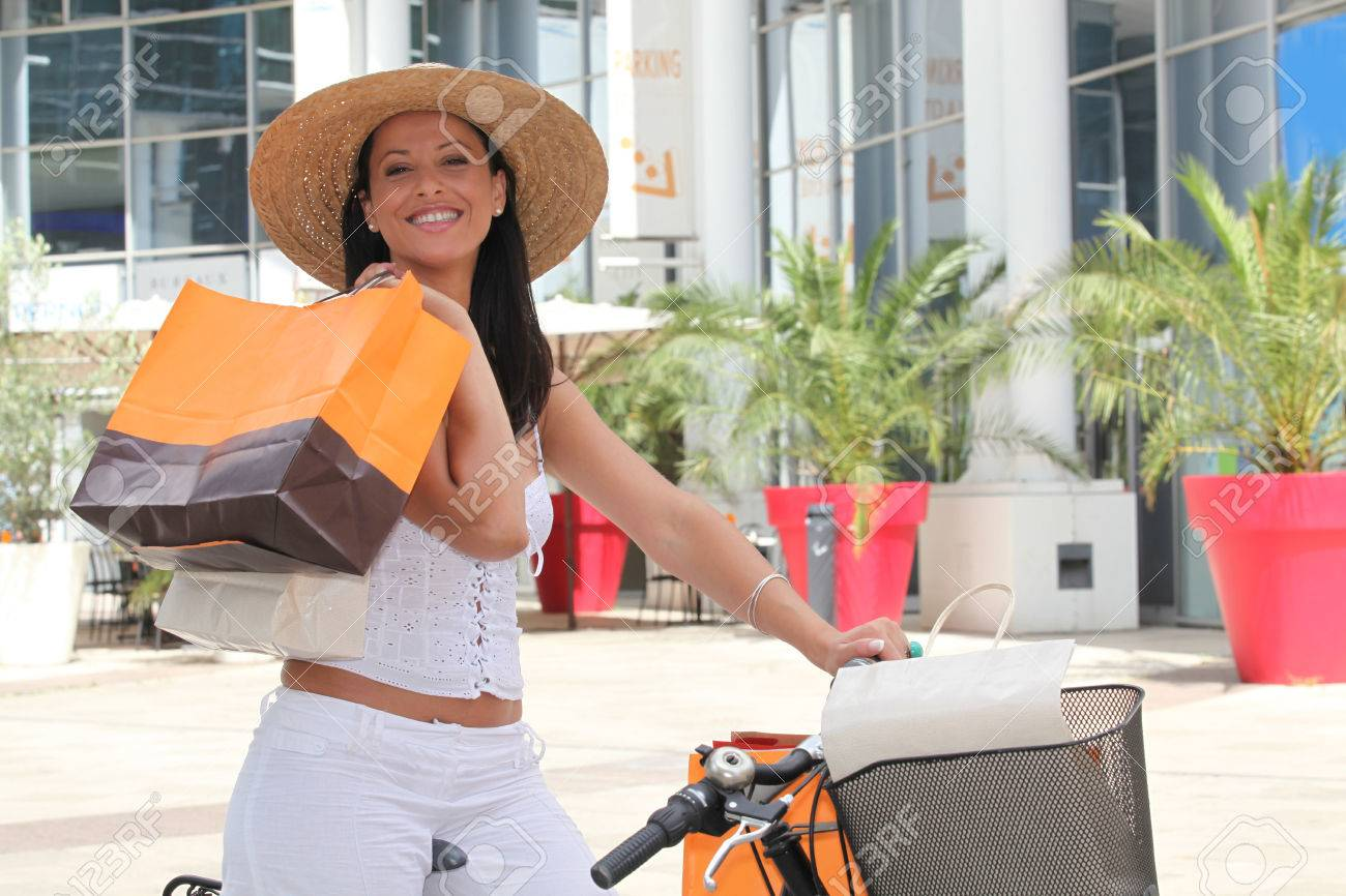 Woman outside a mall with storebags and a bike Stock Photo - 22886644