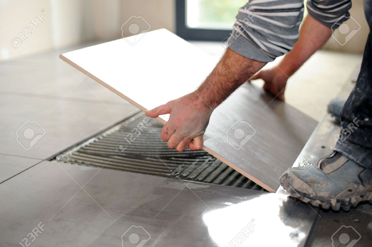 Man laying floor tiles stock photo picture and royalty free image man laying floor tiles stock photo 23874071 dailygadgetfo Choice Image