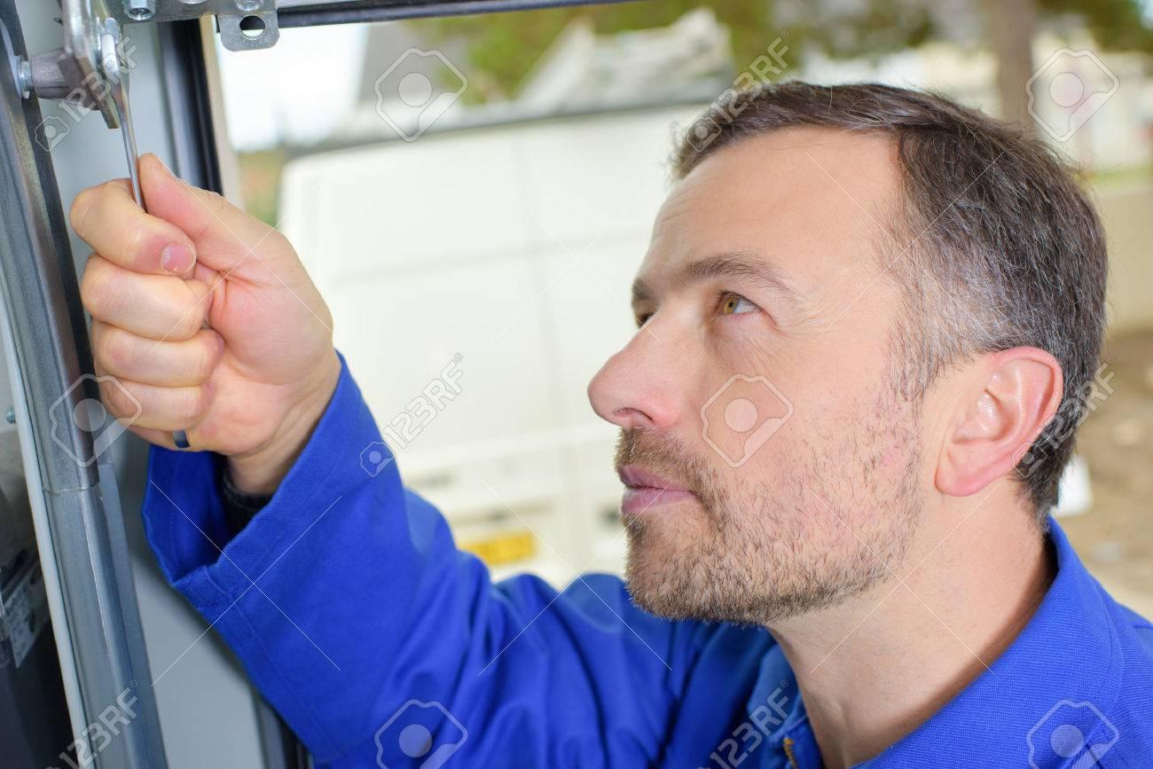 Man installing a garage door Stock Photo - 42709549