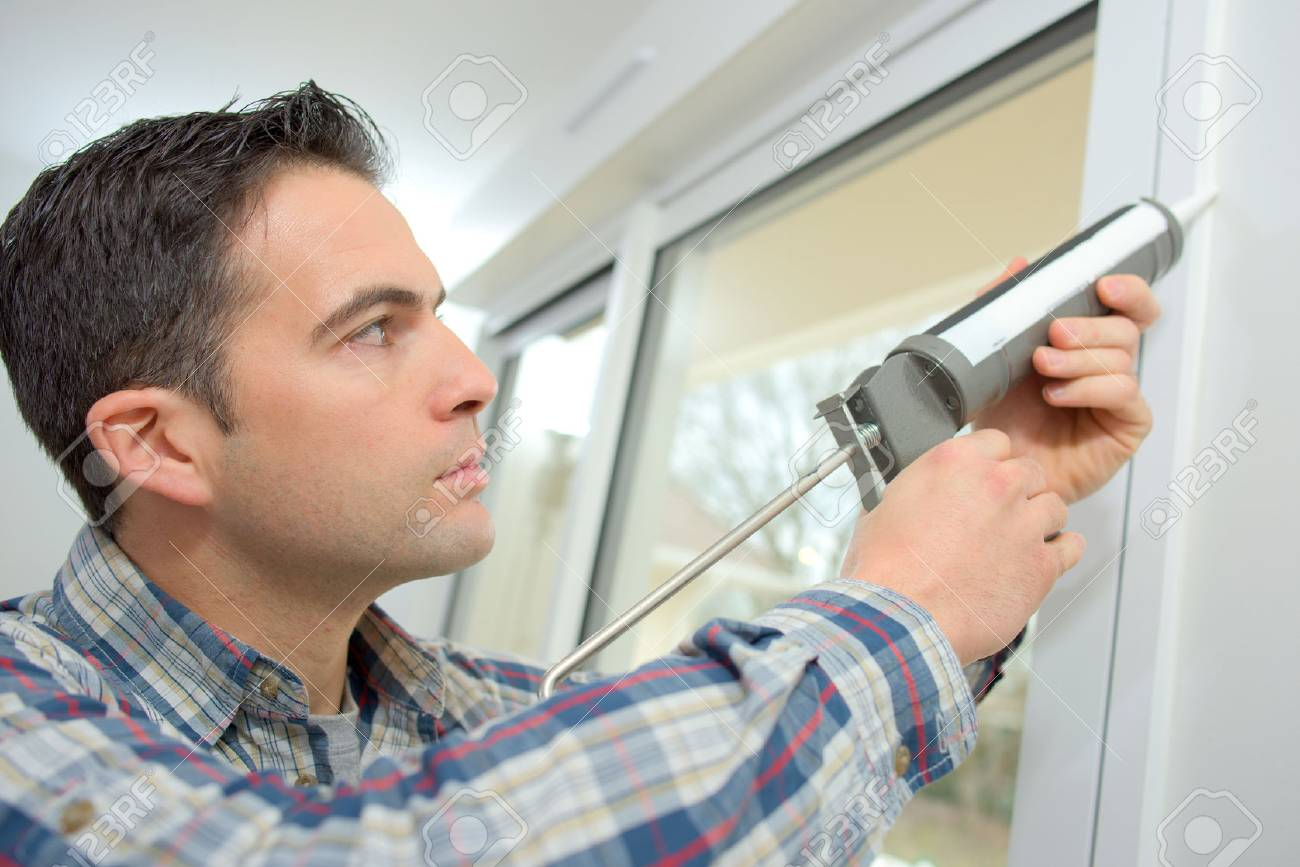Handyman caulking a window Stock Photo - 44934022
