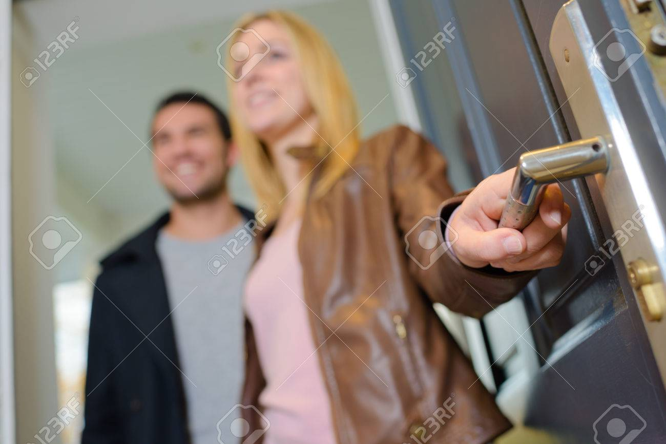 Couple opening a door Stock Photo - 44941044
