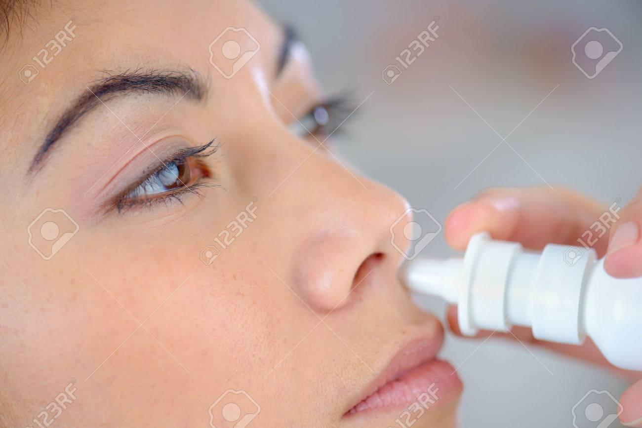 Woman using a nasal spray Stock Photo - 45183591