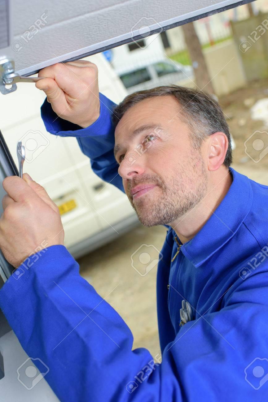 Man installing a garage door Stock Photo - 45379896