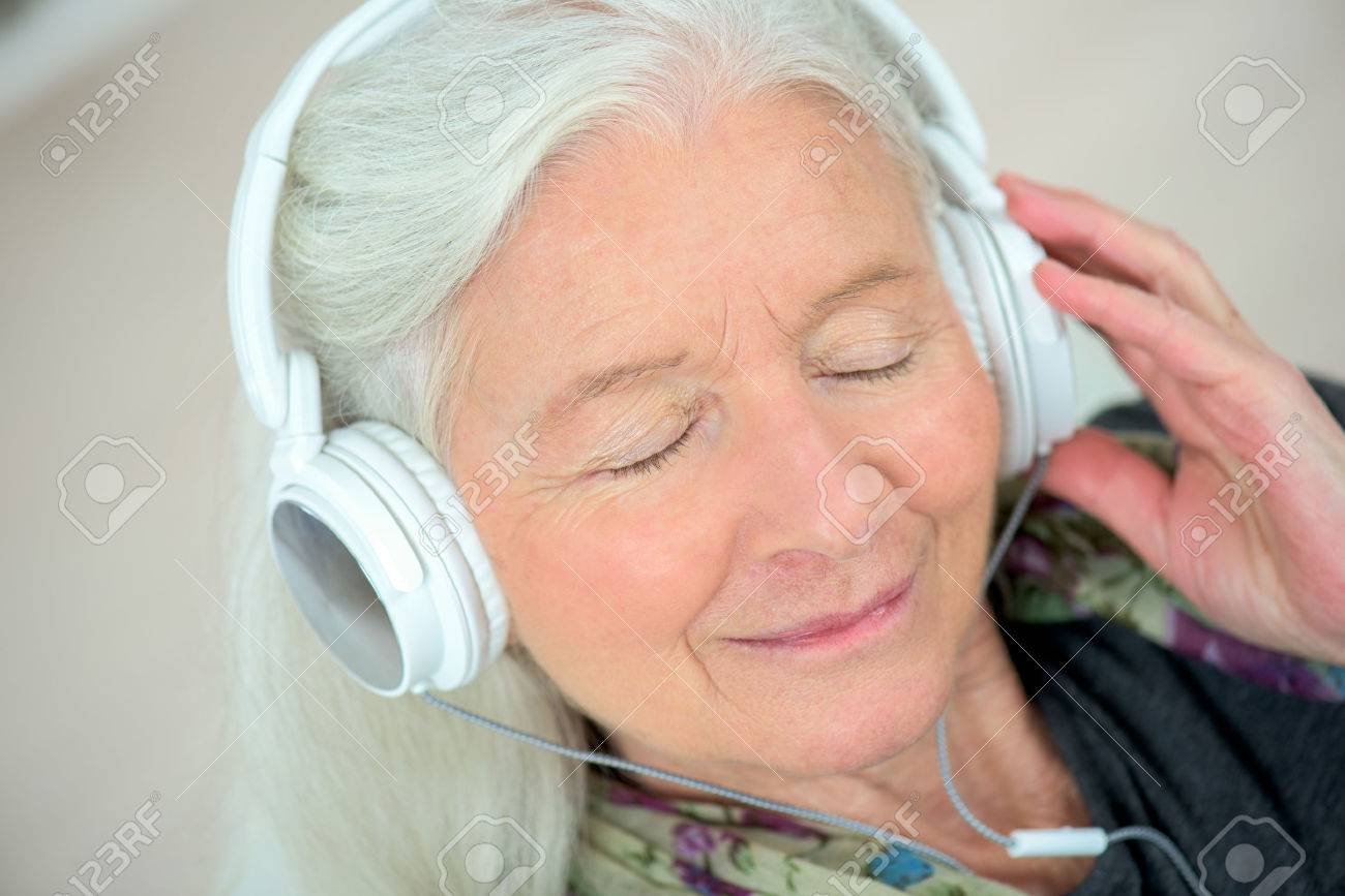 Old lady with headphones on Stock Photo - 46099319