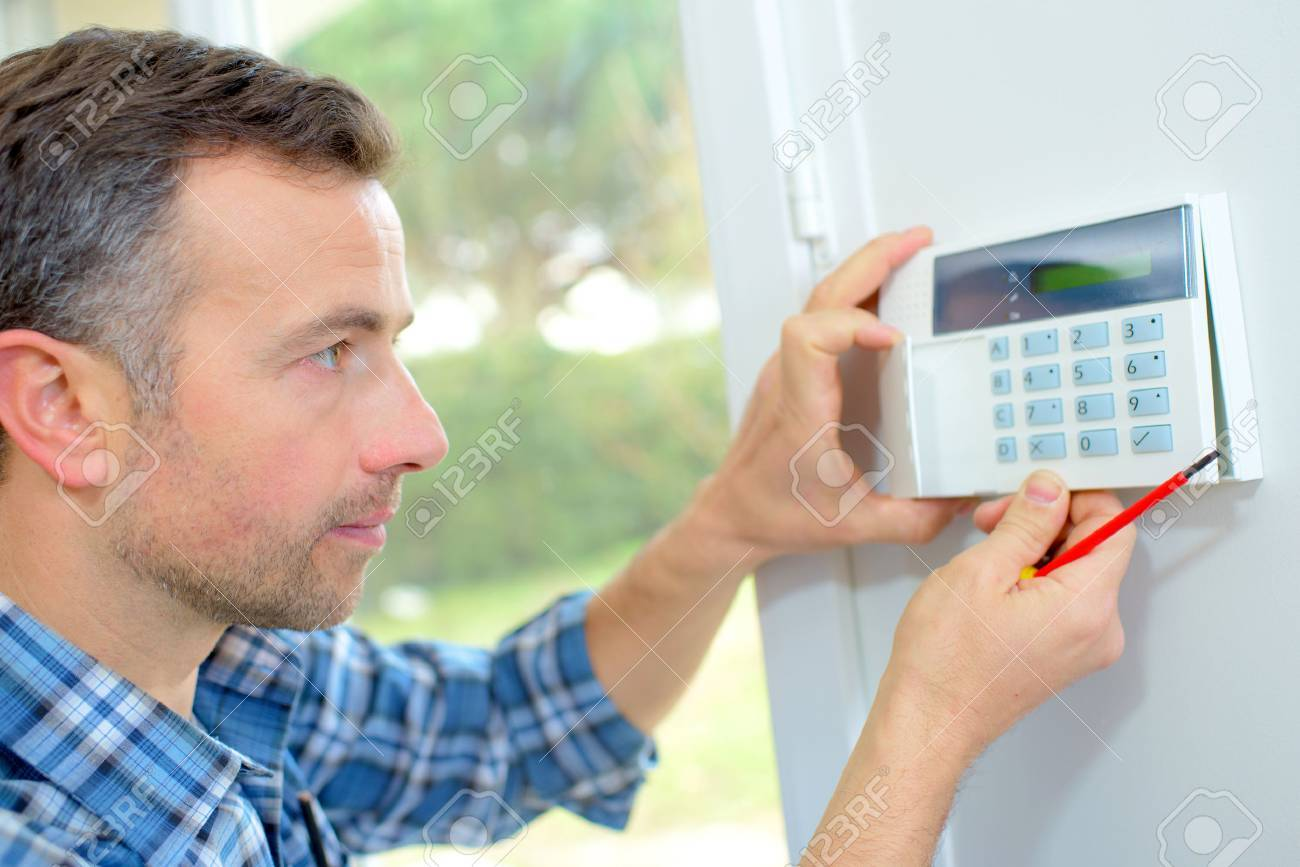 Electrician fitting an intrusion alarm Stock Photo - 46955012