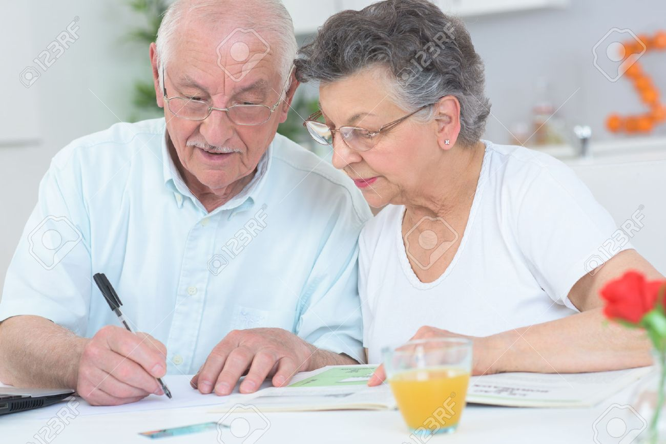 Elderly couple looking at magazine and taking notes Stock Photo - 49309658