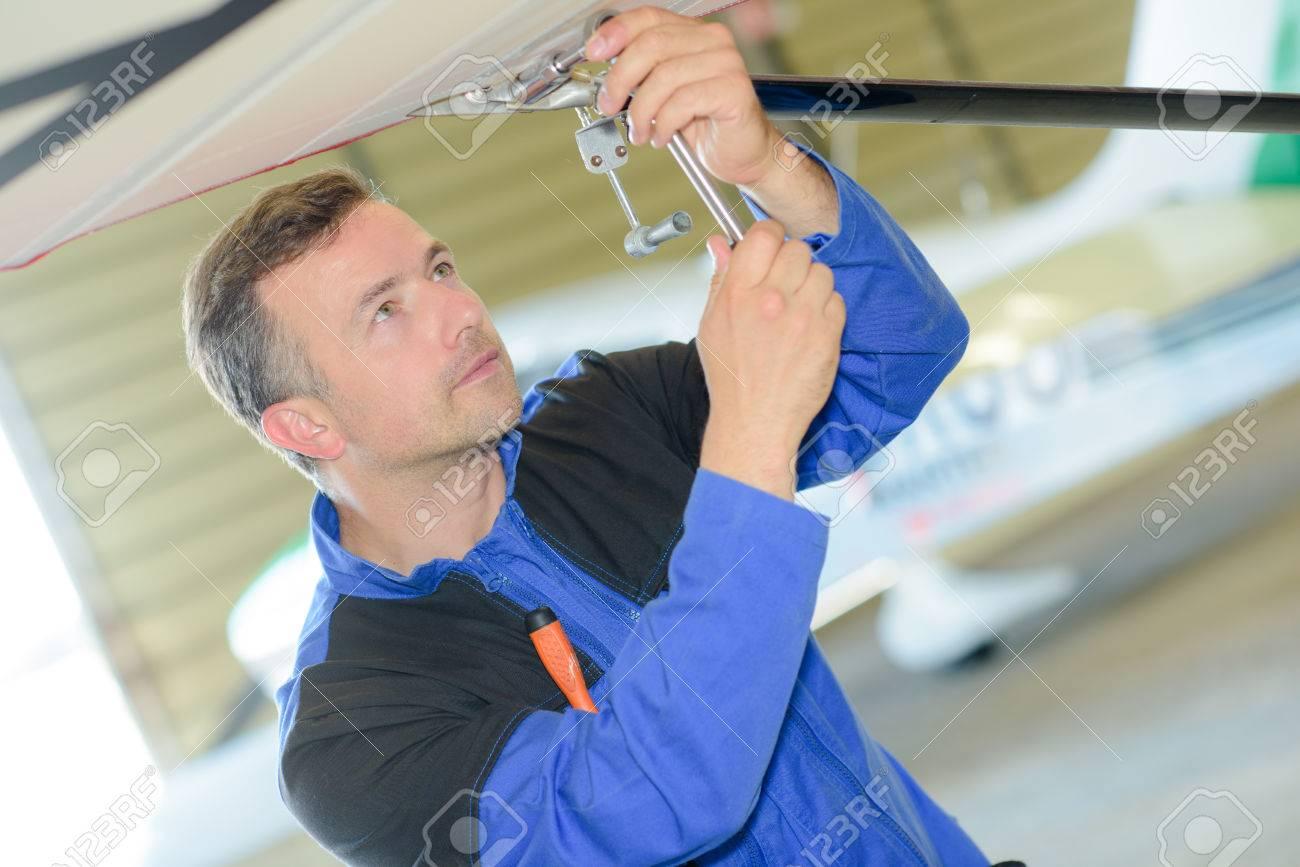L'homme de travail sur la face inférieure d'un aéronef, Banque d'images - 49522986