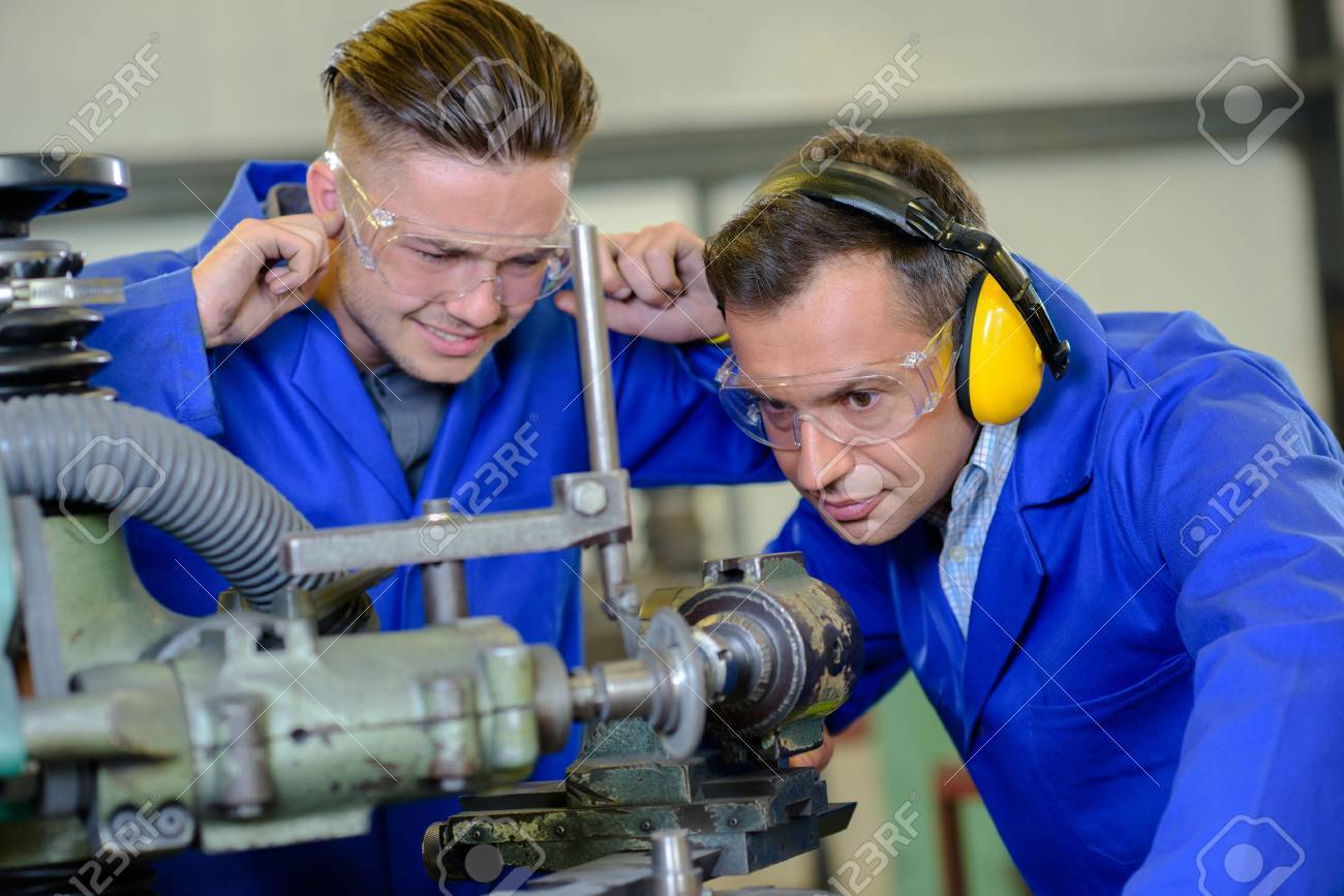 Engineer using machine apprentice with fingers in ears Banque d'images - 51230629