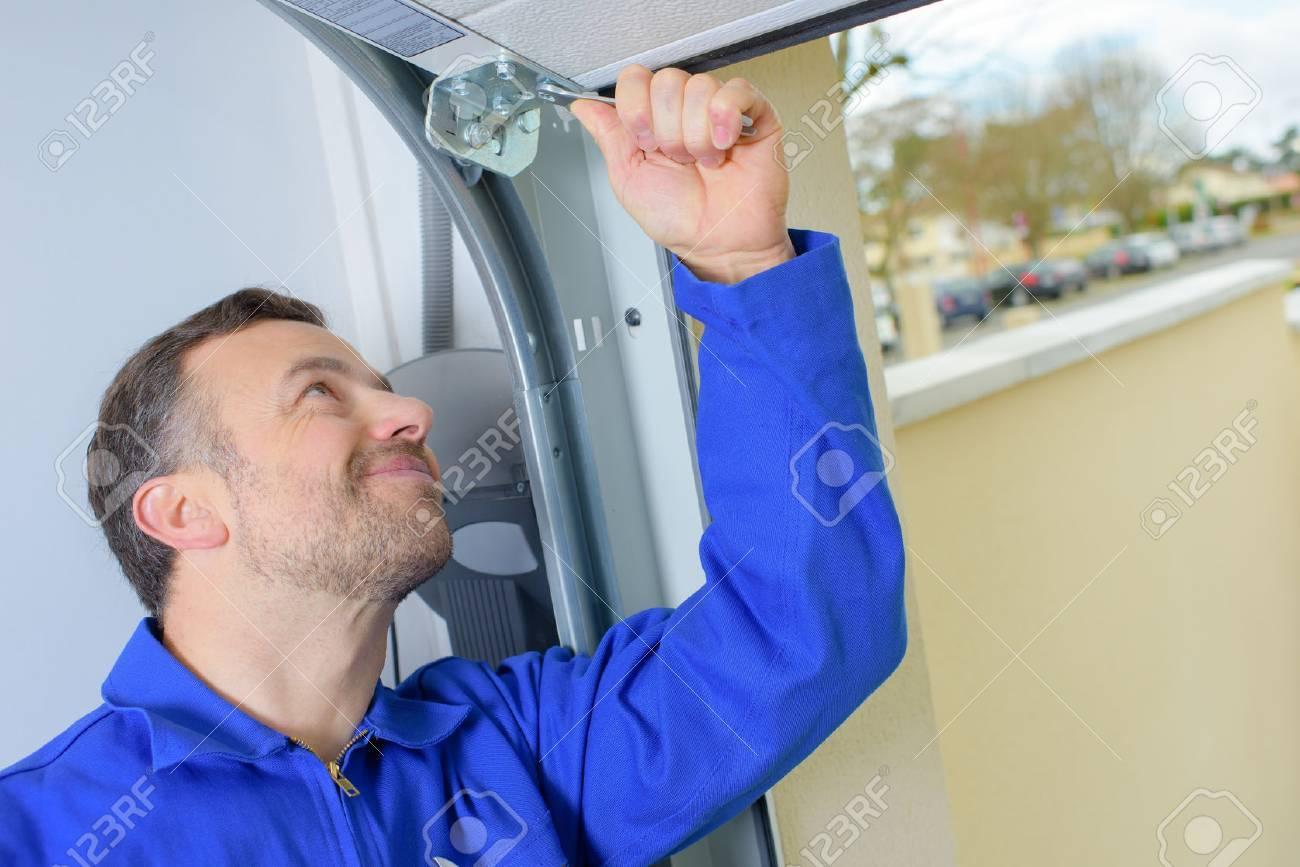 Man installation d'une porte de garage Banque d'images - 57970162