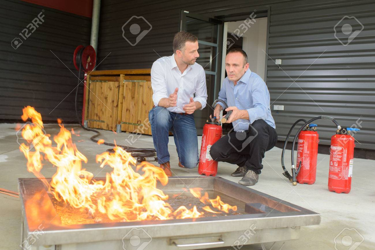 Men training with fire extinguishers Stock Photo - 62931218