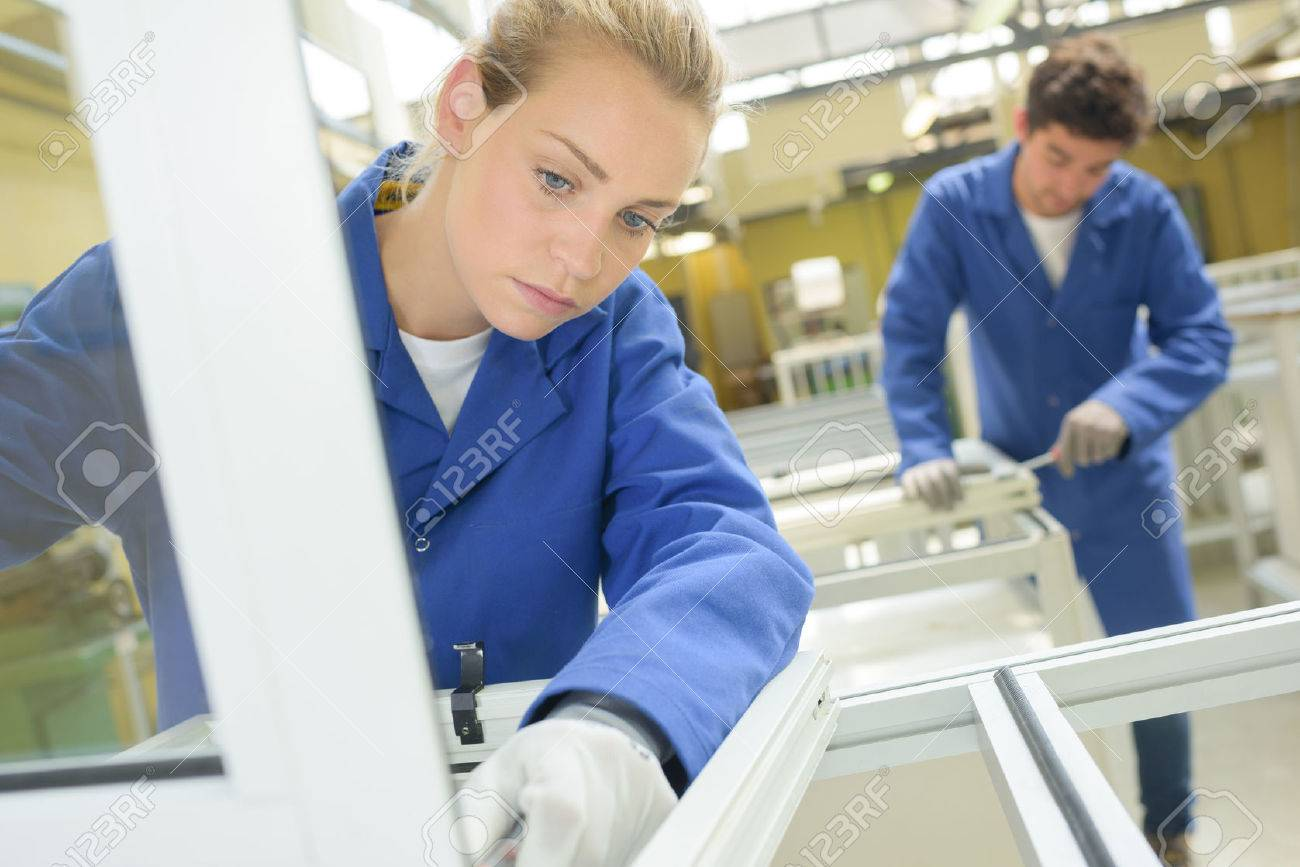 Les jeunes gens qui travaillent dans l'usine de fenêtre Banque d'images - 63101142