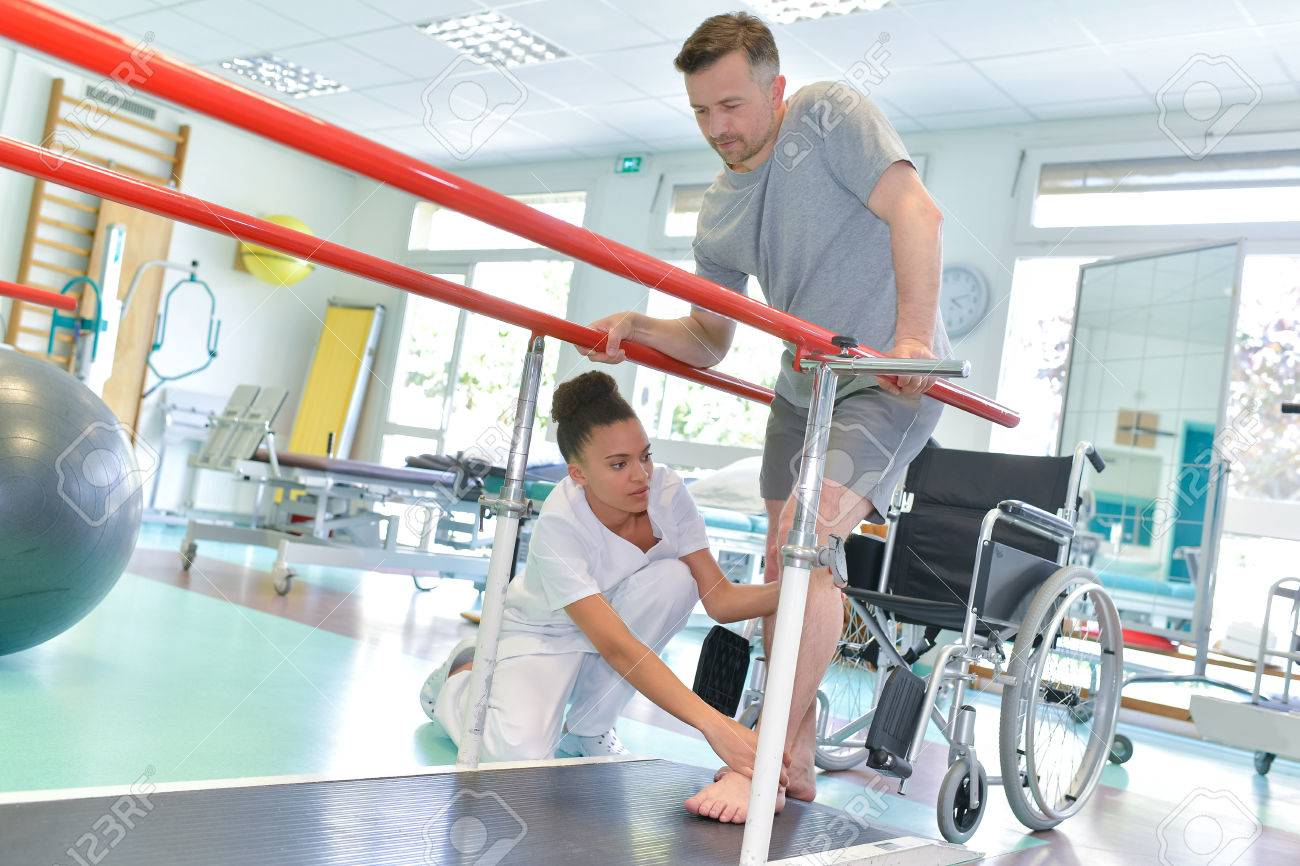 Occupational therapist helping patient to walk - 68521461