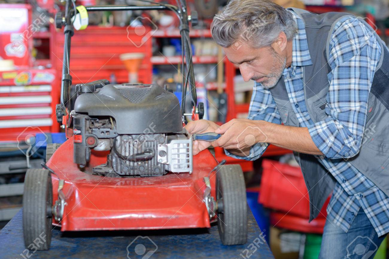worker fixing the lawn mower Stock Photo - 70955529