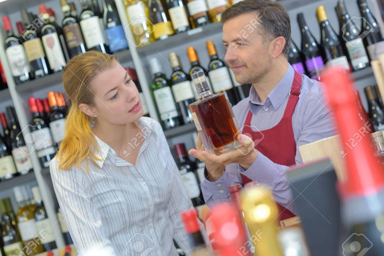 liquor store worker showing bottle to customer stock photo liquor store worker showing bottle to customer stock photo 72293672