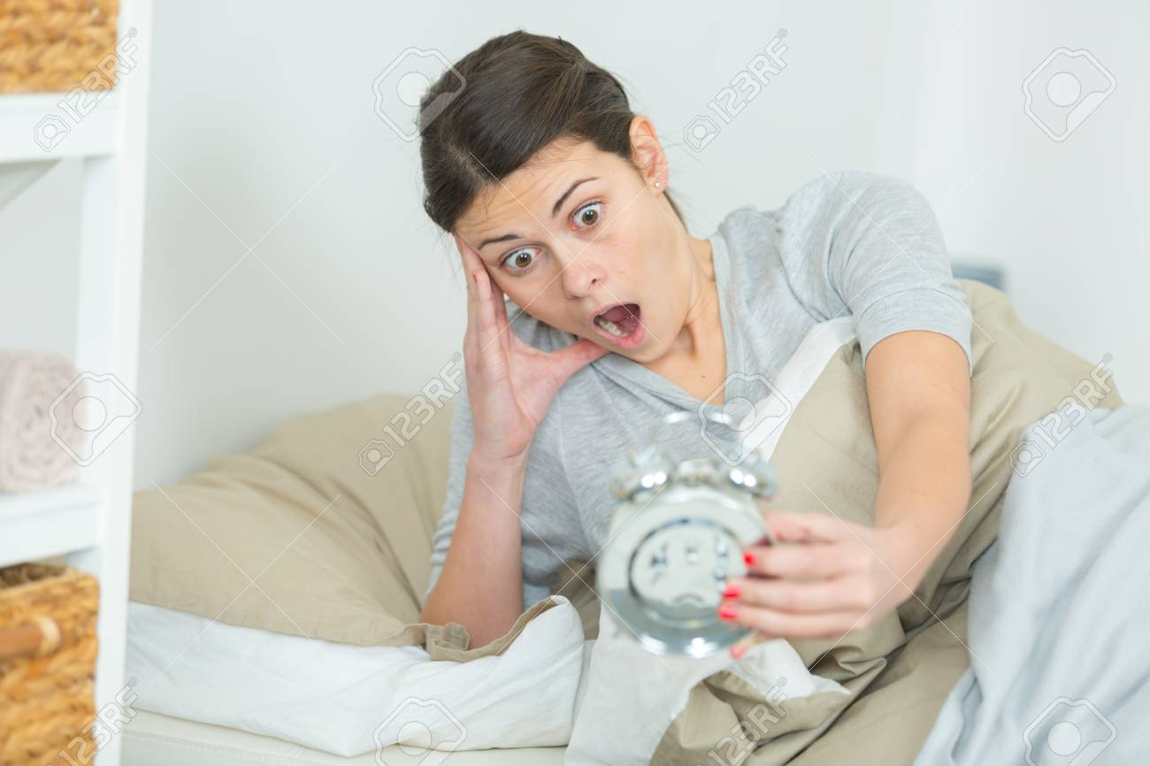 woman in bed looking at alarm clock with shocked expression stock
