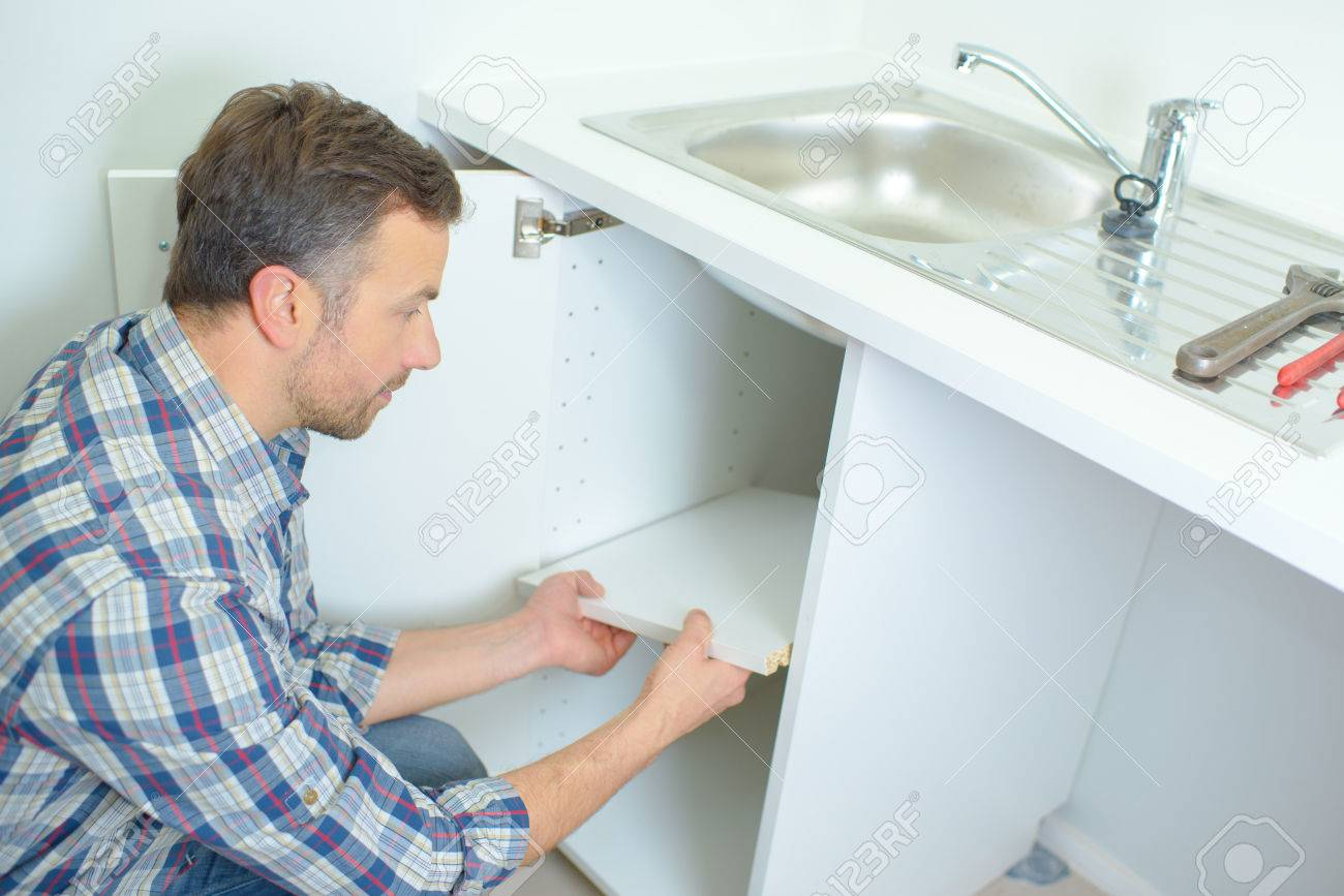 Young Male Plumber Lying On Floor Fixing Sink In Bathroom Stock ...