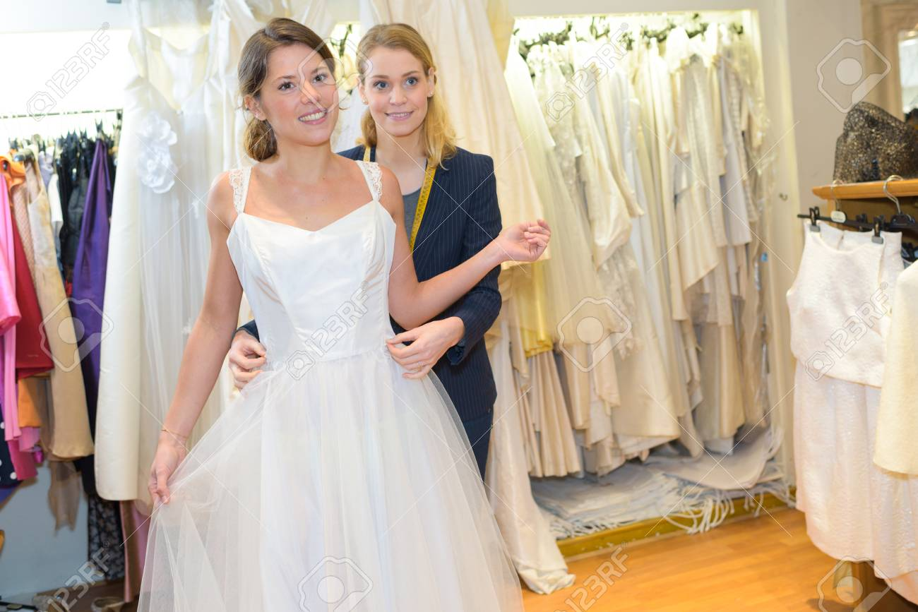 Female Trying On Wedding Dress In A Shop With Assistant Stock Photo ...