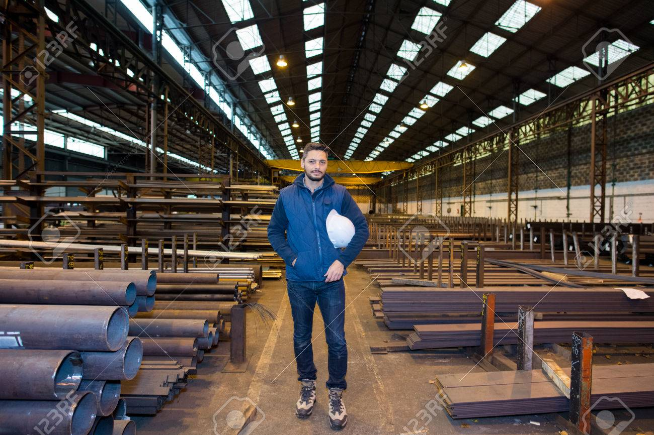 7a5f0782e male worker stood in warehouse stocking metal lengths Stock Photo - 80369862