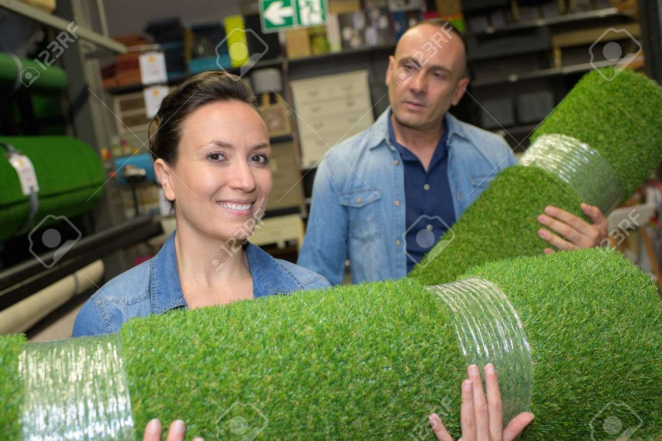 Man and woman holding rolls of artificial turf - 86482691