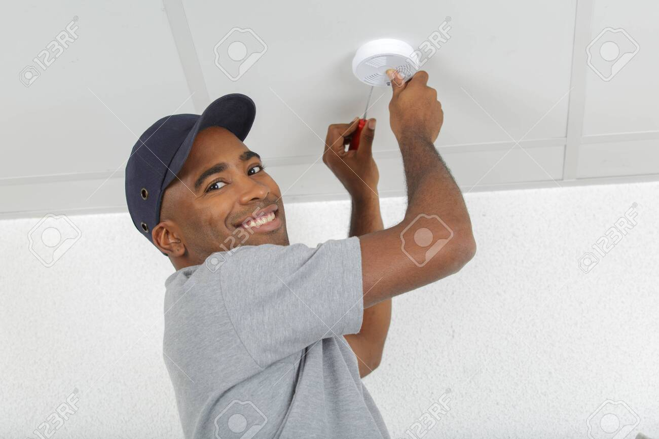 electrician removing battery from smoke detector - 125399496