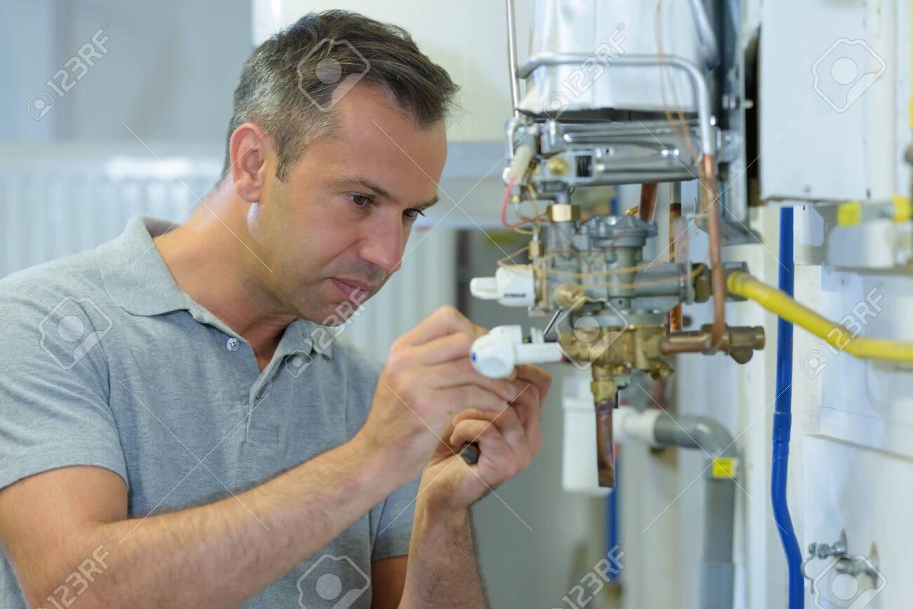 male engineer repairing a gas boiler - 125495867