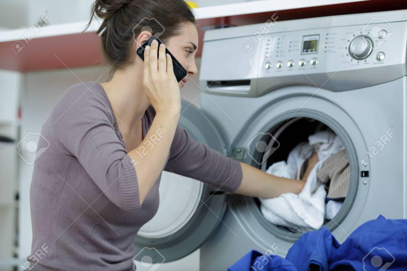 woman wearing white shirt using smart phone near washing machine - 126412016