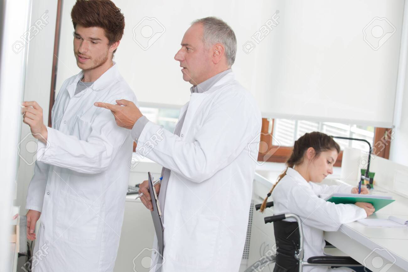 scientists writing note on the board - 126475460
